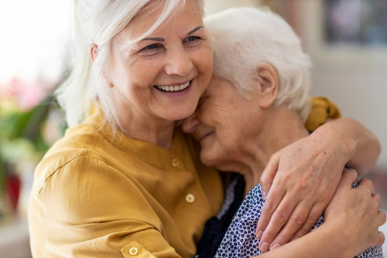 Older women smiling and embracing another senior.