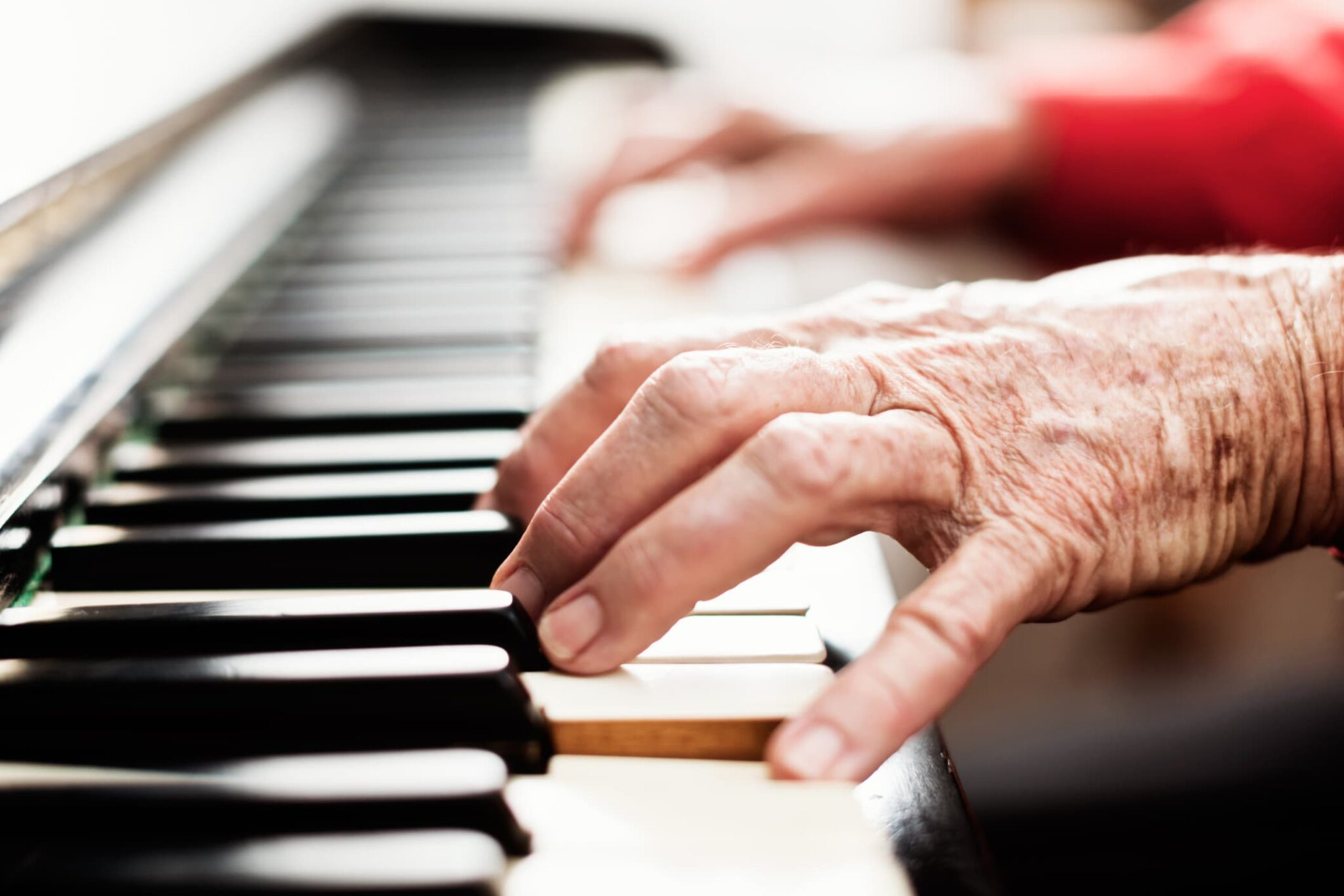 Elderly hands playing a piano pain-free.