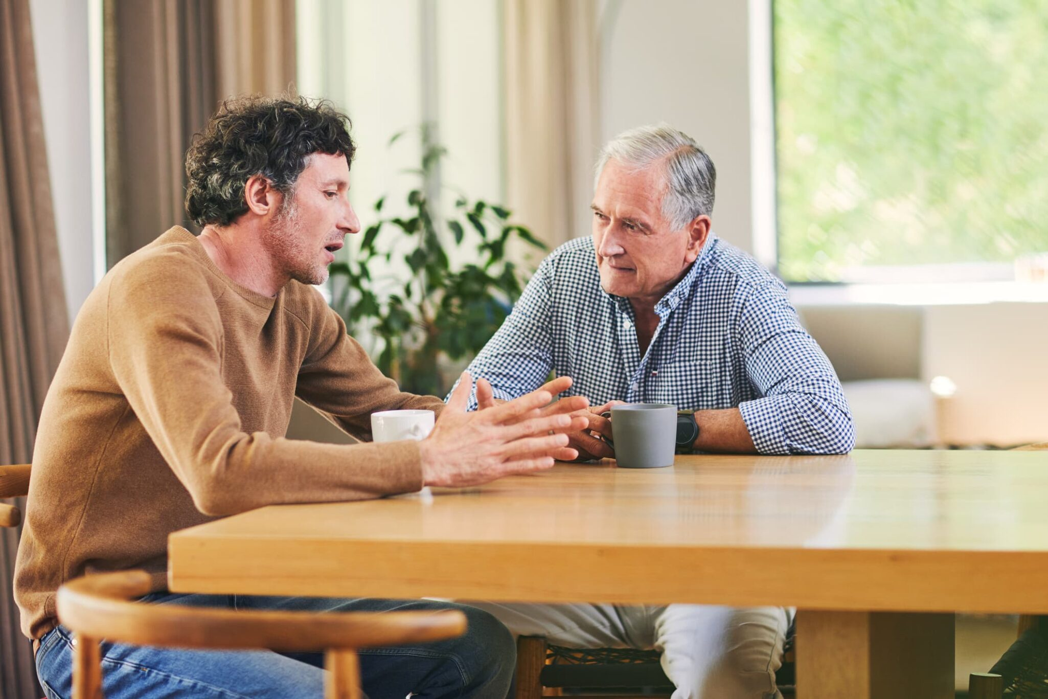 Father and son have a conversation at the dining room table.