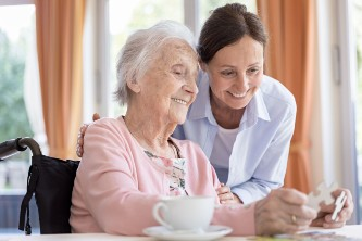 elderly memory care patient putting together a puzzle with a caregiver