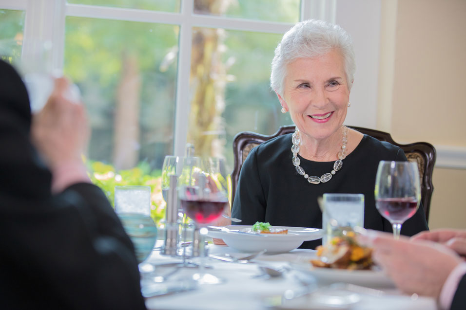 A senior women enjoying a meal in the dining area of her luxury senior living community